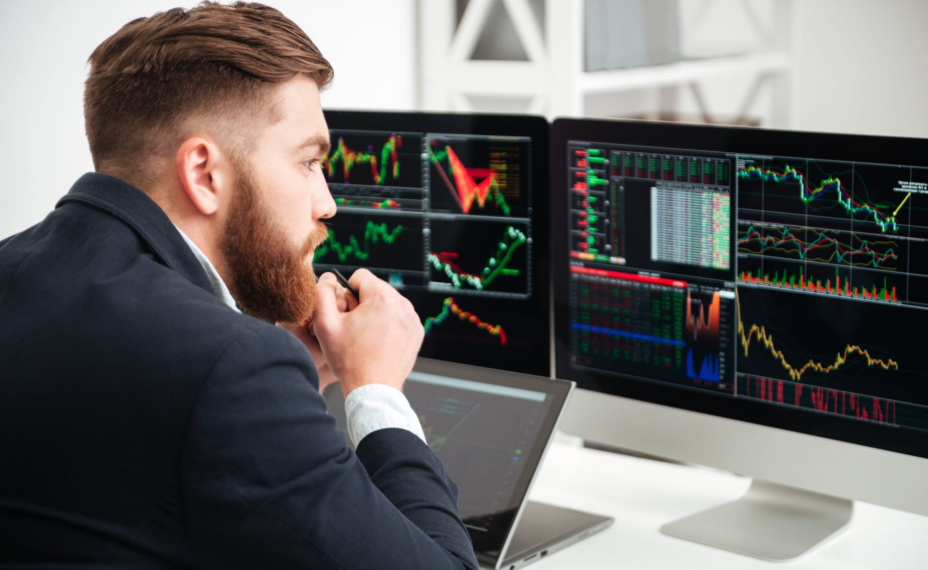 Back view of thoughtful bearded young businessman sitting and woking with graph and charts on computer