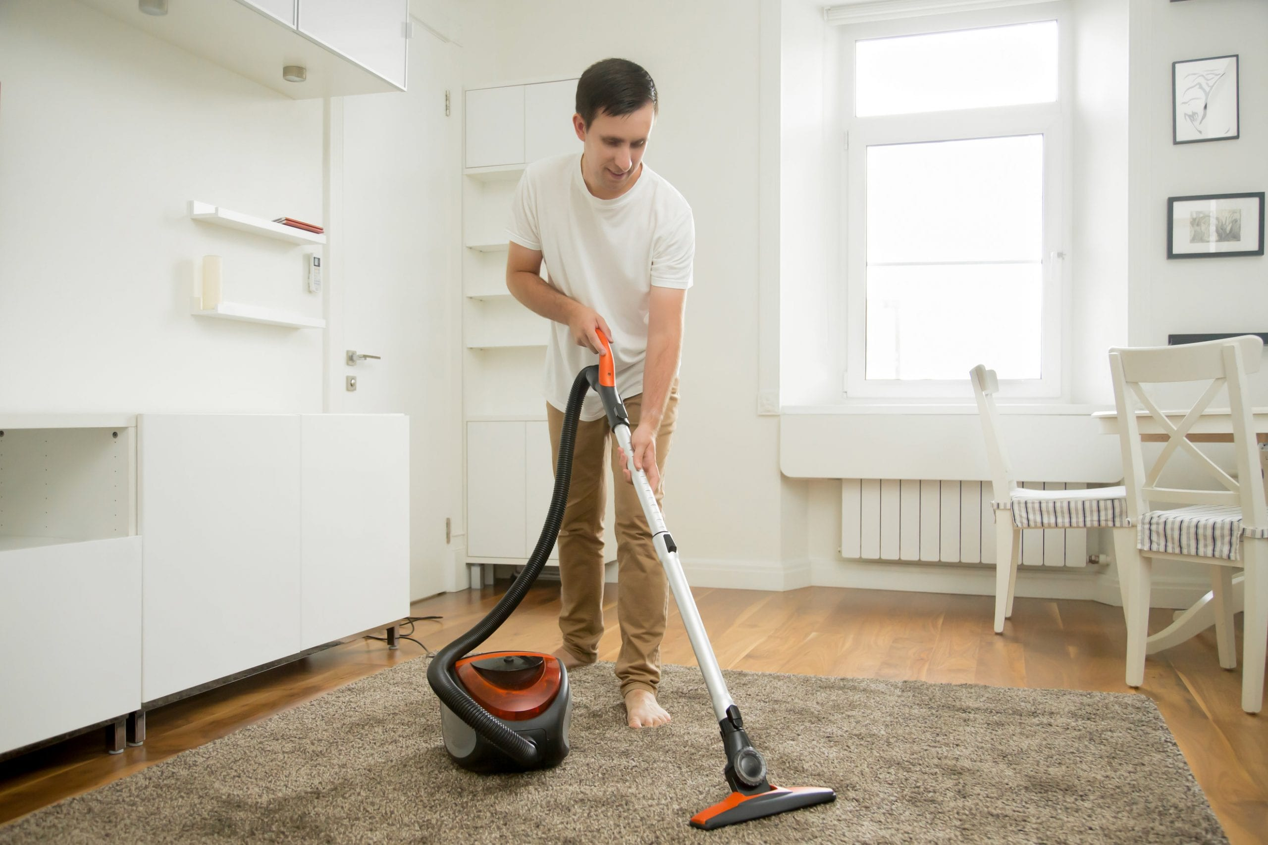 Happy smiling man vacuum cleaning the carpet in the living room, modern scandinavian interior. Busy, cleaning day. Home, housekeeping concept.